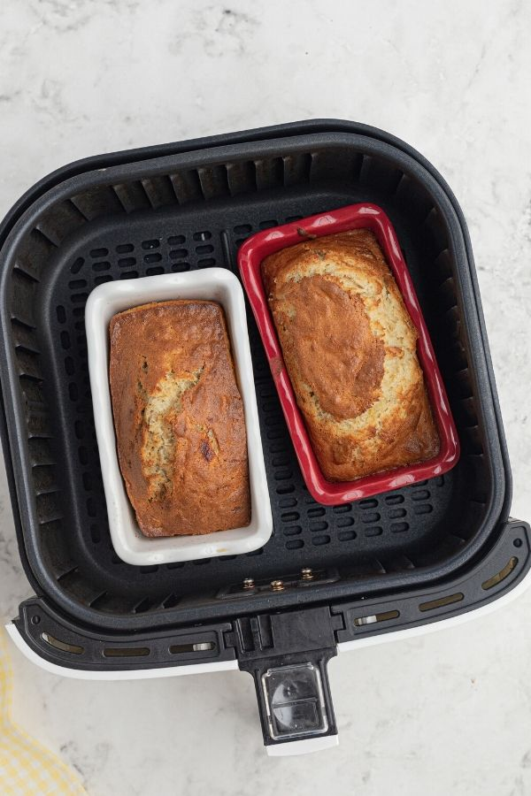 Uncooked loaves of bread in small loaf pans inside of an air fryer basket. One is red and the other is white.