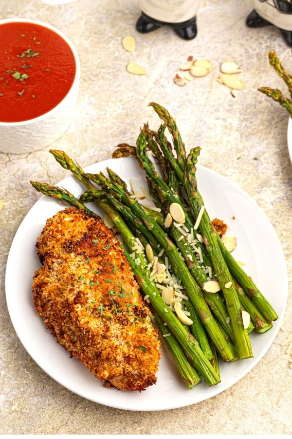 Cooked asparagus on a white plate with chicken.