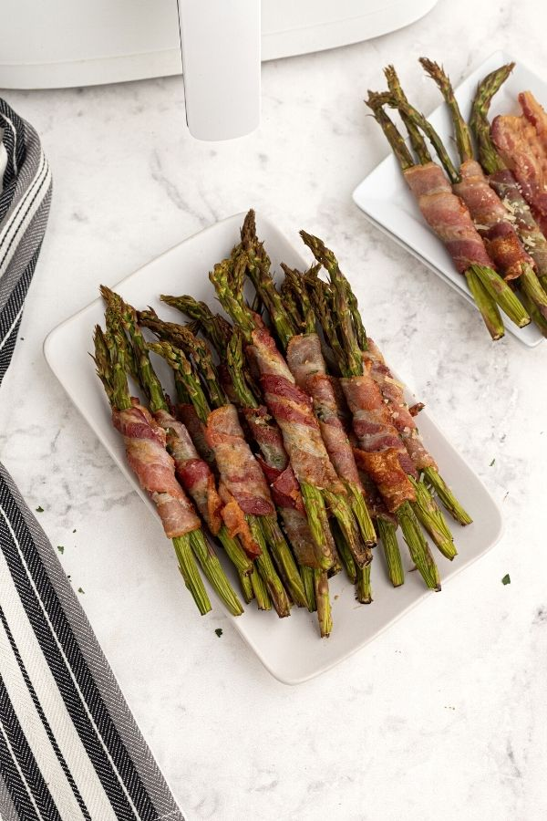 Cooked bacon wrapped asparagus on a white plate