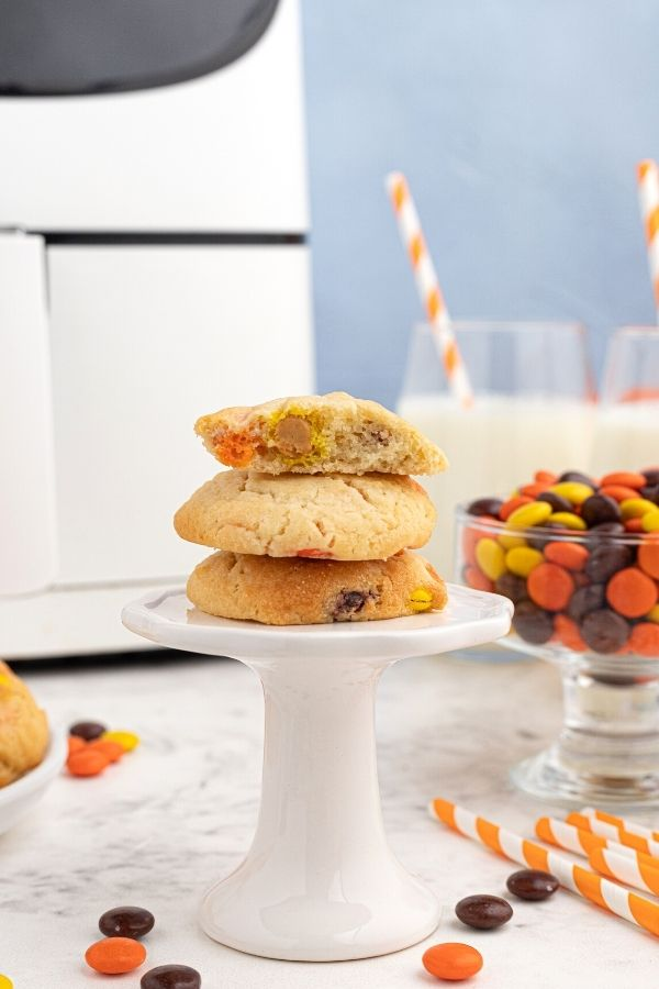 Air Fryer Sugar cookies stacked on a small white pedestal, with a bowl of Reese's Pieces on the table, in front of an air fryer.