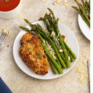 Cooked parmesan crusted chicken served with green asparagus on a white plate.