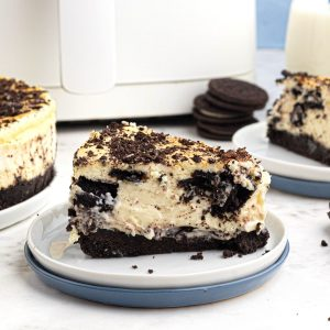 creamy slice of Oreo cheesecake served on a white plate in front of an air fryer.