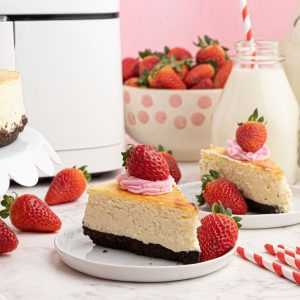 Creamy sliced piece of cheesecake, with a chocolate crust, served with strawberries on a white plate in front of an air fryer.