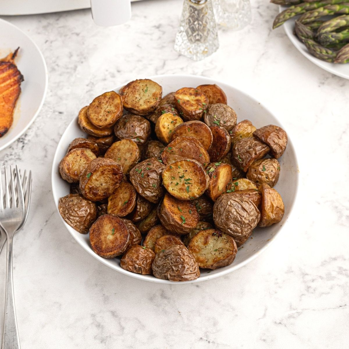 Roasted potatoes in a white bowl. Cooked and cut in half, topped with seasonings.