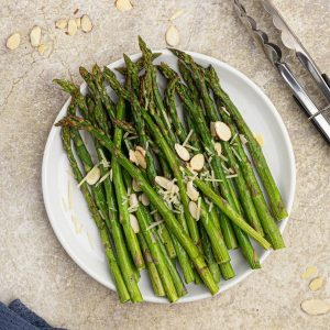 Cooked asparagus and a white plate, seasoned with salt and pepper, topped with slivered almonds and parmesan cheese.