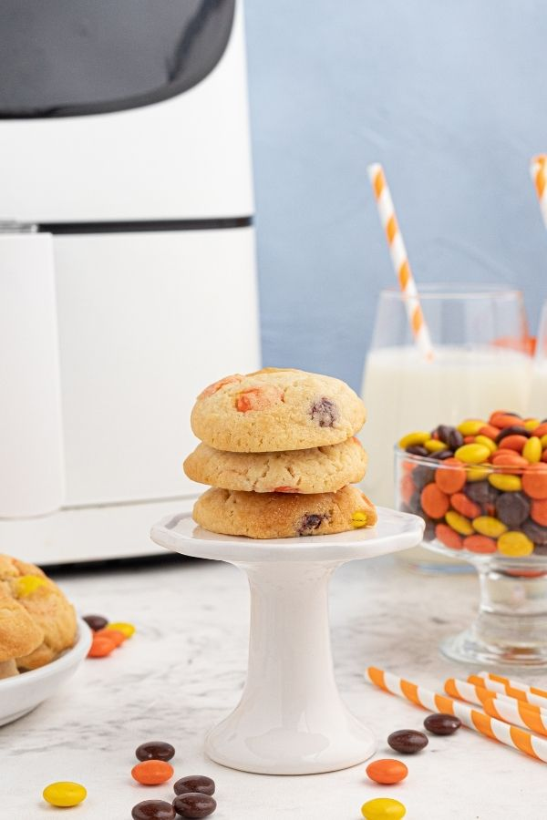 Stacked sugar cookies on a white pedestal, in front of an air fryer.