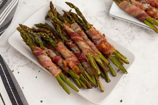 Cooked asparagus with crispy bacon wrapped around each stalk served on a white plate