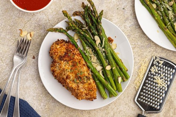 Parmesan Crusted Chicken on a white plate with cooked asparagus.