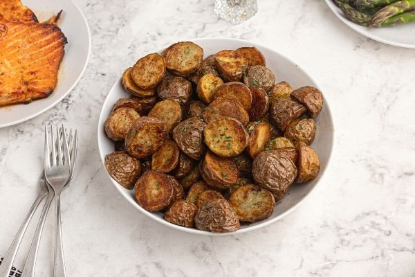 Crispy cooked potatoes, in a white bowl, served next to main dish.
