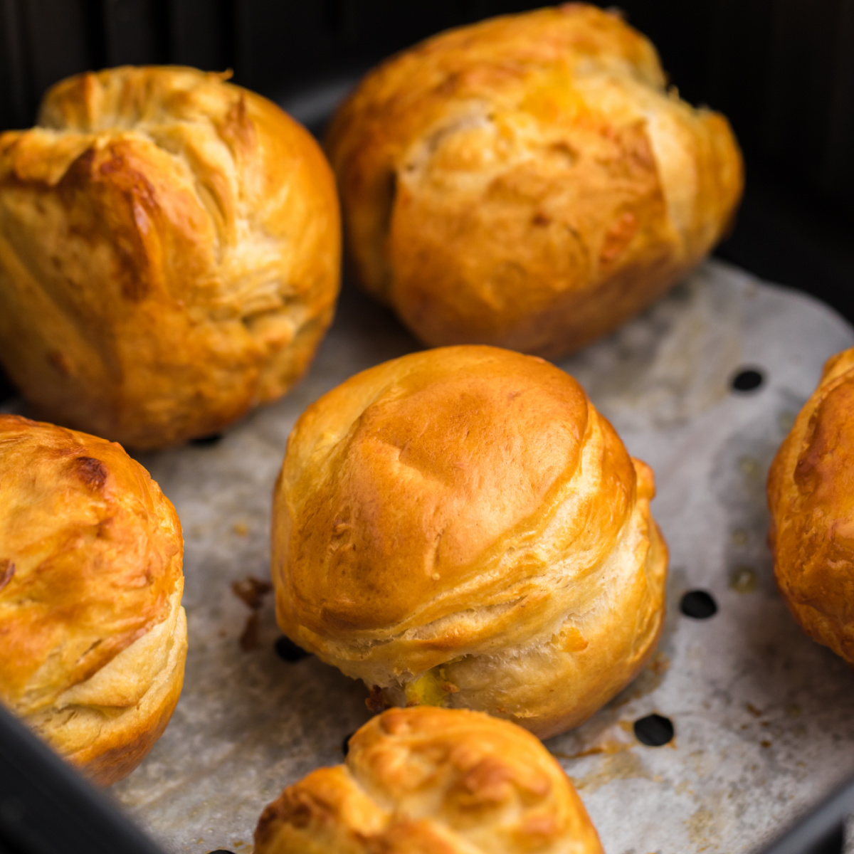 Air Fryer Biscuit Bombs on parchment paper in the basket of the Air Fryer.