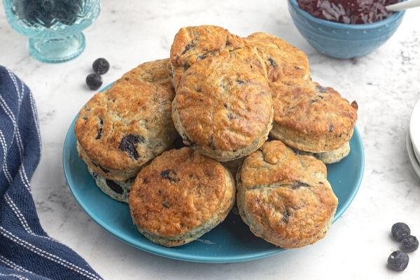Air fryer blueberry scones on a light blue plate, with scattered blueberries around the plate.