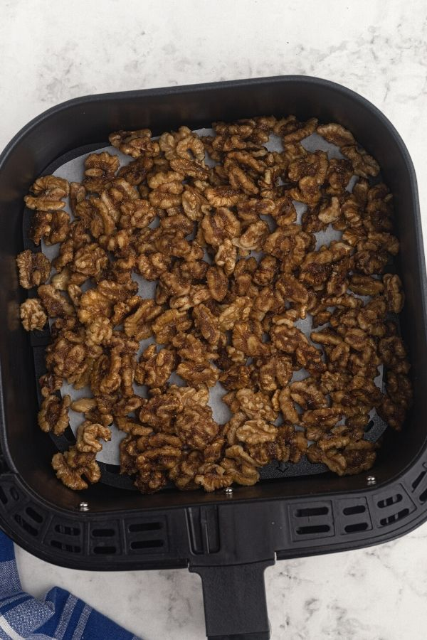 Walnuts in the air fryer basket, after being heated with the melted butter and sugars with seasonings.