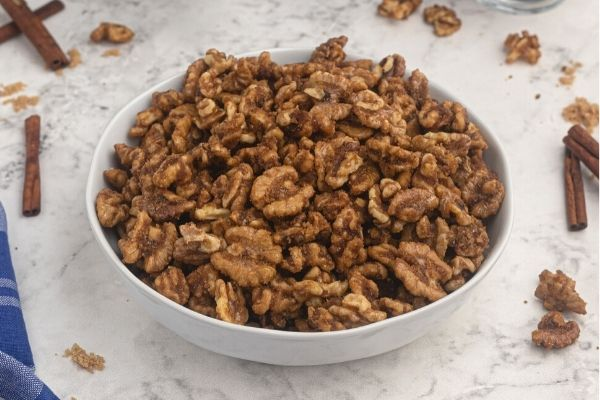 Candied walnuts served in a white bowl with cinnamon sticks and walnuts scattered on a white marble counter.