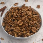Candied Walnuts, served in a white bowl with cinnamon sticks and scattered walnuts on the table