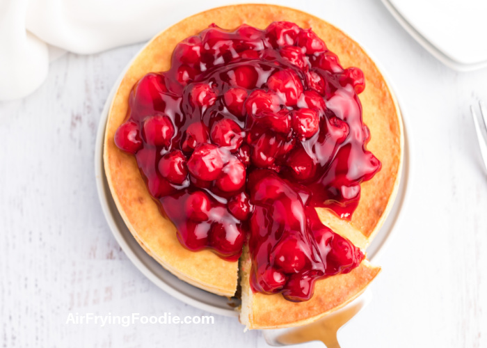 Overhead shot of a cheesecake on a white plate and topped with cherries, with a slice being removed.