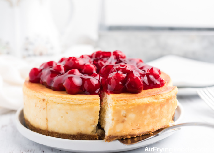 Classic cheesecake made in the Air Fryer, sliced and topped with cherries.