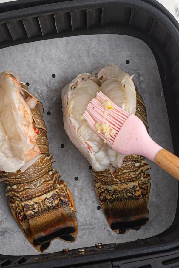 Uncooked lobster tails in the air fryer basket, being brushed with melted butter and minced garlic.