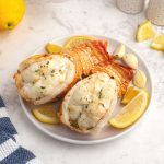 Cooked, lobster tails, topped with garlic and parsley, served on a white plate with lemon wedges.