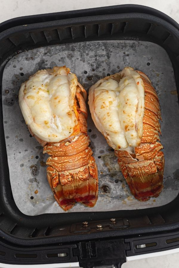 Cooked lobster tails in the air fryer, sliced and brushed with butter and garlic.