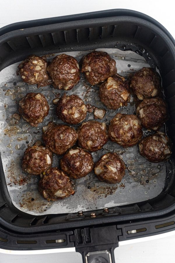 Cooked  hamburger meat, shaped into meatballs, in an air fryer basket lined with parchment paper.