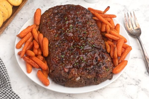 Air Fryer Meatloaf on a white plate with baby carrots around the meatloaf.