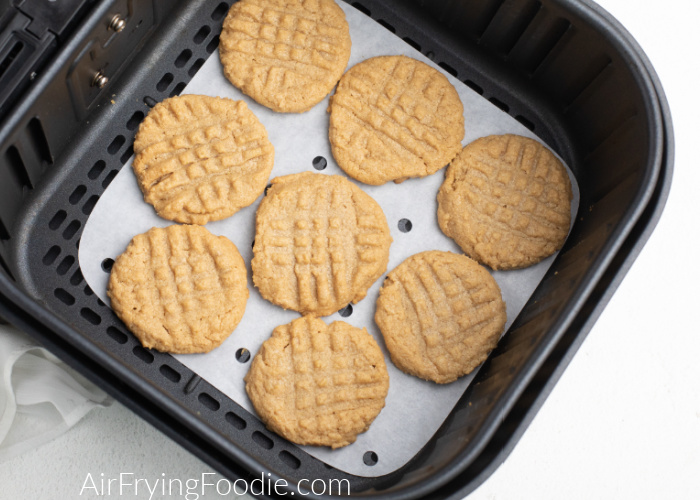 Peanut Butter cookies on a piece of parchment paper in the Air Fryer basket.
