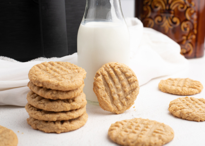 Peanut butter cookies on a white table with a glass of milk and an Air Fryer in the background.