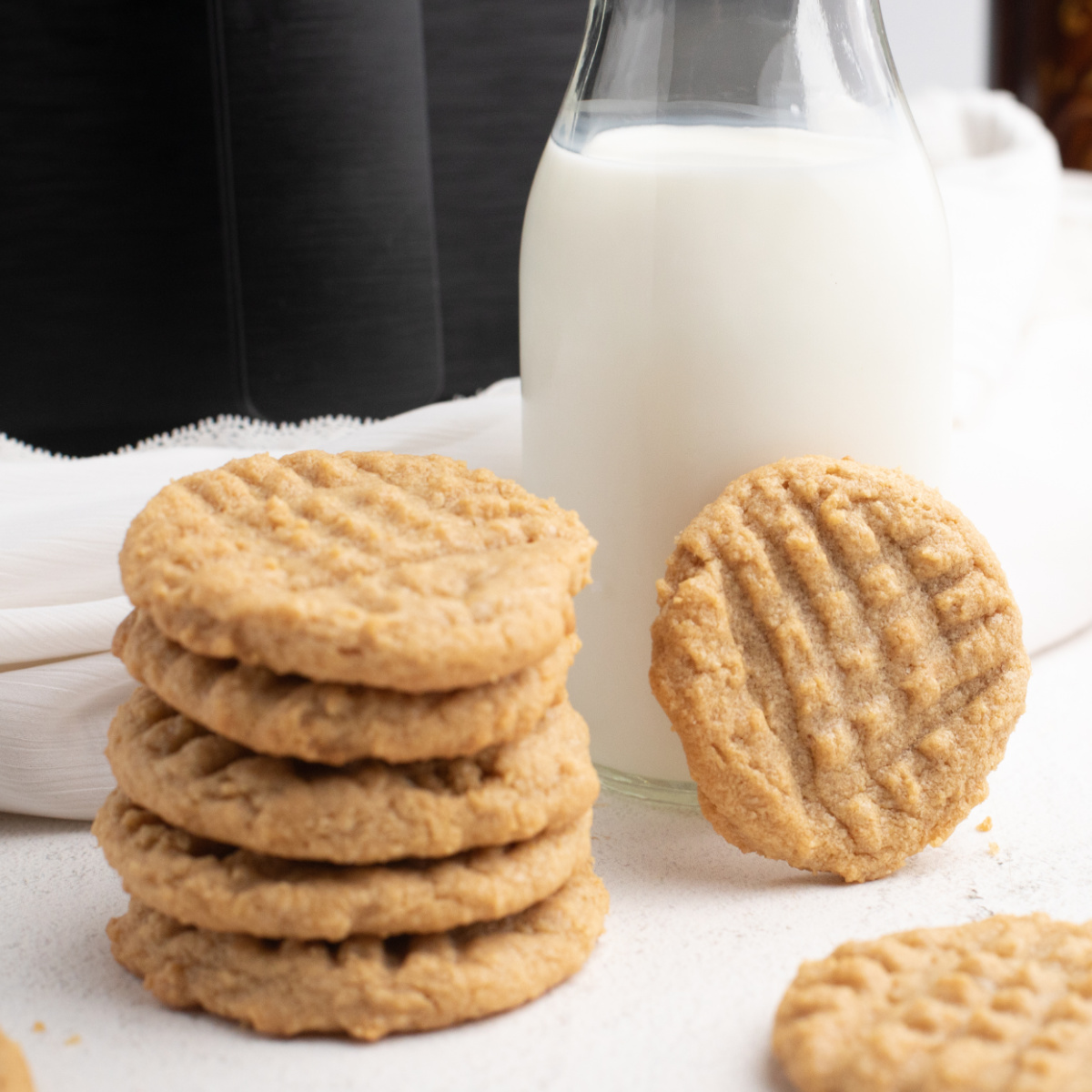 A stack of peanut butter cookies made in the Air Fryer with a glass of milk and the Air Fryer in the background.