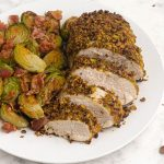 Cooked and sliced pistachio crusted chicken served with brussel sprouts on a white plate