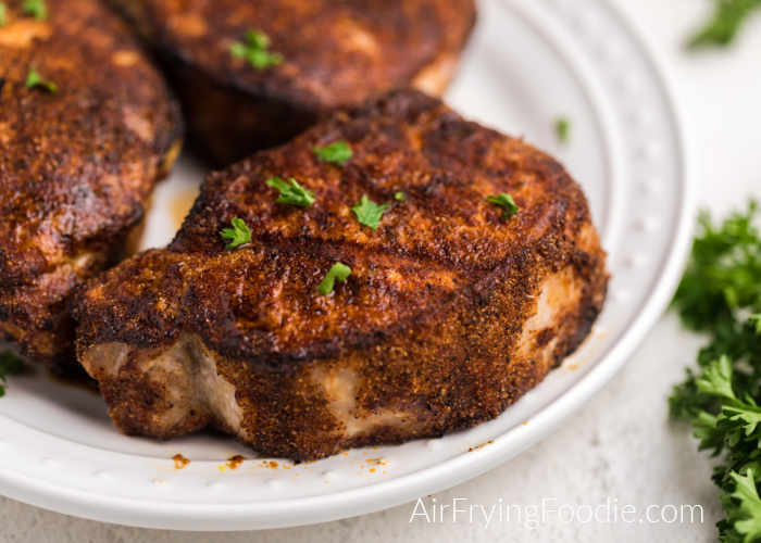 Thick cut pork chops on a white plate and topped with chopped parsley.
