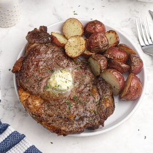 Juicy and cooked ribeye steak on a while plate. Served with red potatoes.