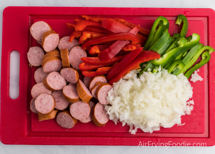 Cutting board with sliced sausage, peppers, and diced onion.