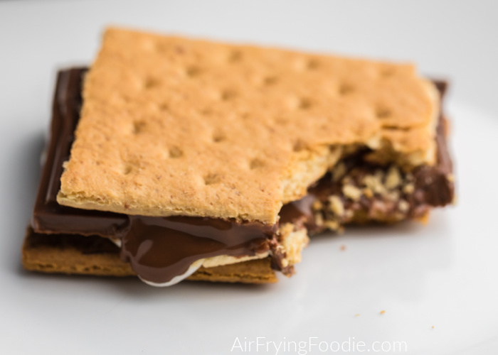 S'more with a bite missing on a white plate.