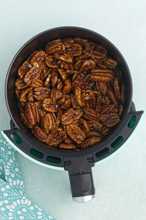 Spiced pecans before being cooked, marinating in the air fryer basket.