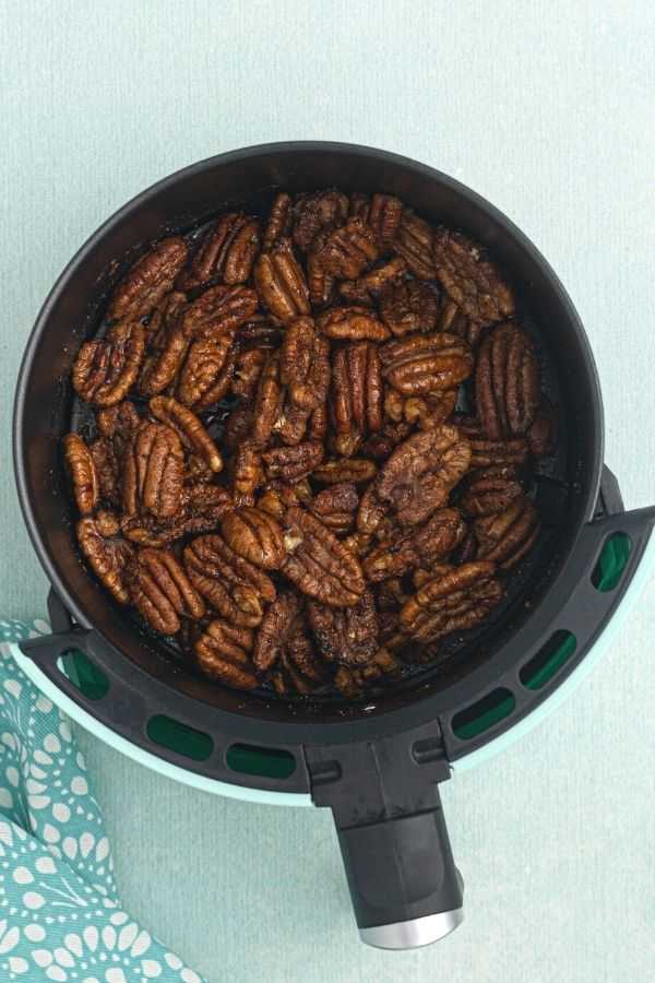 Spiced air fryer pecans, after being cooked in the air fryer, resting in the air fryer basket.