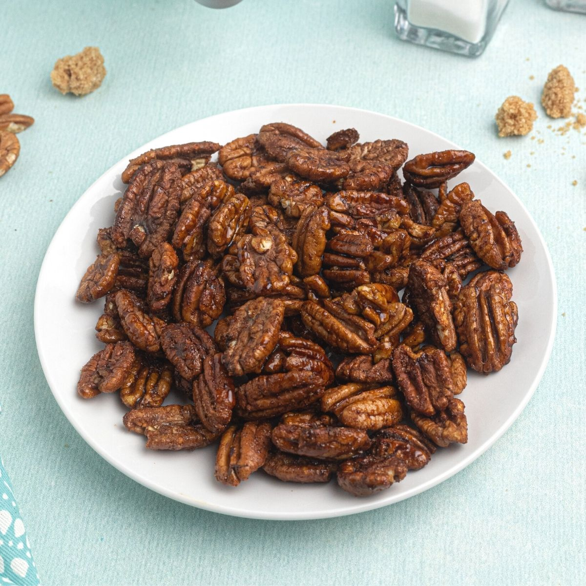 Cooked pecans, served on a white plate, in front of an air fryer, with scattered pecans and brown sugar around the plate.