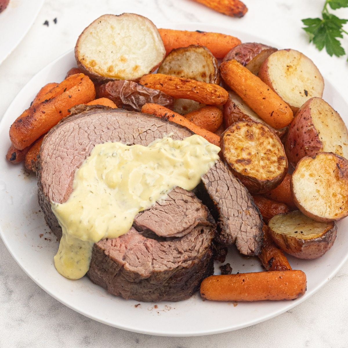 Air fryer top round roast, cooked and topped with bernaise sauce. Served with air fryer roasted potatoes and carrots.