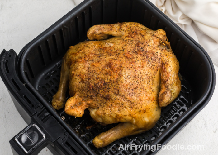 Fully cooked 4 ½lb Air Fryer Whole Chicken in the basket.