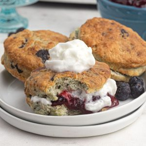 Air fryer blueberry scones, filled with jam and cream, served on a white plate.