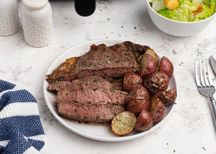 Juicy, cooked and sliced ribeye steak, in front of an air fryer, served on a white plate, with potatoes.