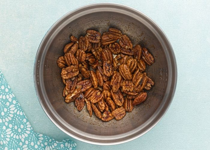 Pecans in a metal mixing bowl, sitting in the soy sauce and seasonings before being cooked in the air fryer.