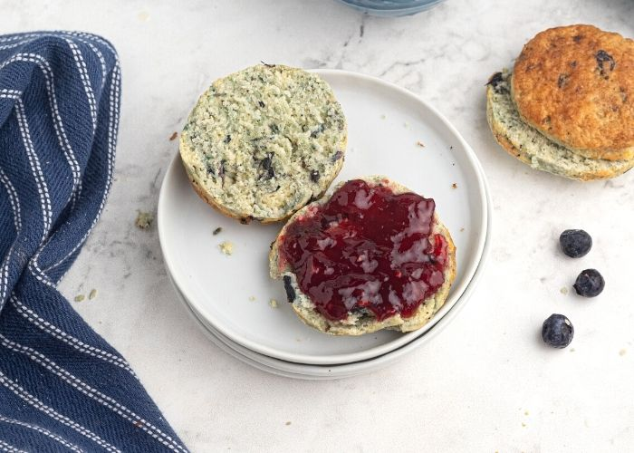 Blueberry scone, sliced in half and served with jam on a white plate.