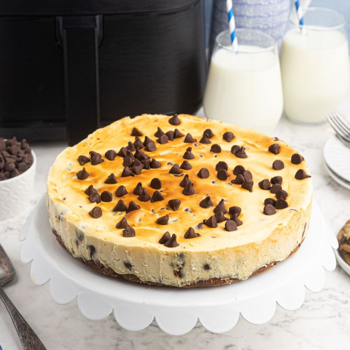 Air Fryer Chocolate Chip cheesecake on a white cake stand, in front of an air fryer.