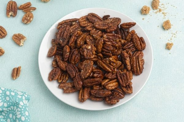 Spiced Pecans served on a white plate with scattered pecans and brown sugar on the table.