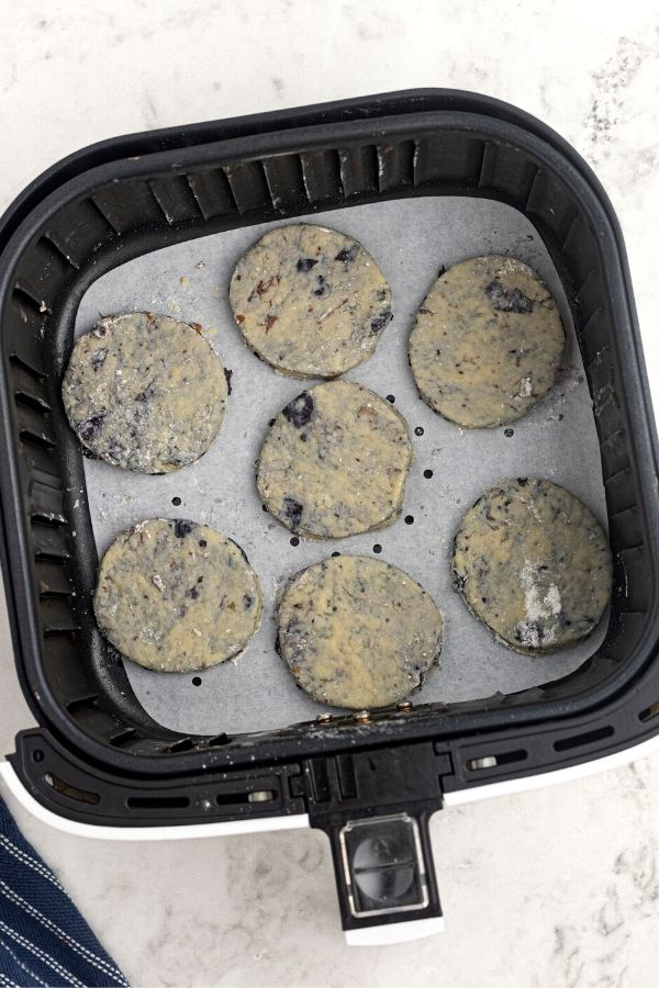 Uncooked blueberry scones in an air fryer basket.