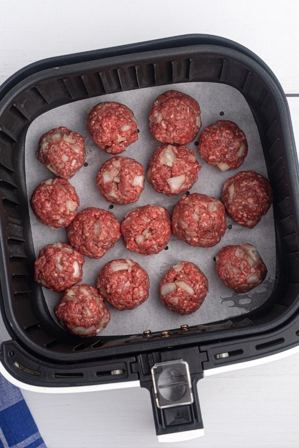 Rolled meatballs placed in an air fryer basket before cooking.