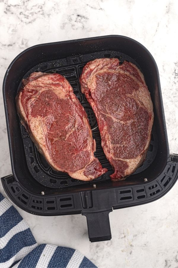 Juicy and thick uncooked ribeye steaks in an air fryer basket, coated with olive oil and seasonings.