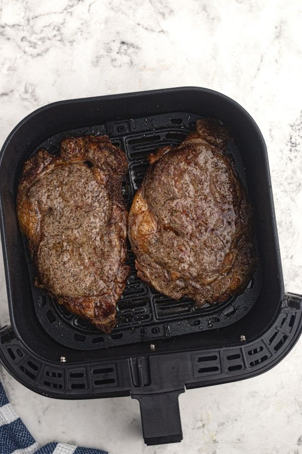 Juicy and thick ribeye steaks, cooked in an air fryer basket.