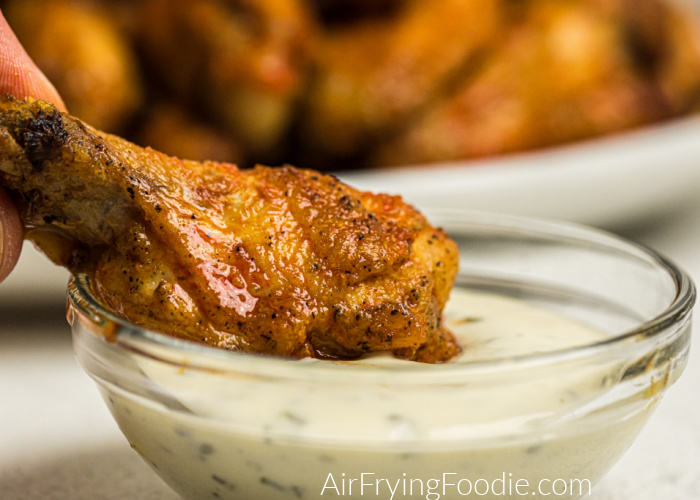 Air Fried Chicken Wing covered in buffalo sauce being dipped in Marie's creamy Ranch dressing.