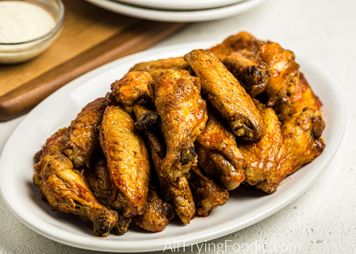 Buffalo Chicken Wings made in the Air Fryer and piled on a white plate ready to serve.